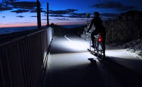 A Cyclist lights the road ahead with bright lights